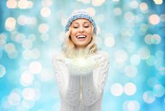 Woman in winter hat holding fairy dust on palms Stock Photos