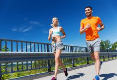 smiling couple running at summer seaside - stock photo