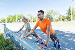 close up of happy couple doing push-ups outdoors - stock photo