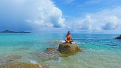 Young beautiful yoga teacher in yellow bikini doing yoga on the rock in the sea Stock Footage