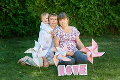 Young family having a picnic with windmills on the grass Stock Photos