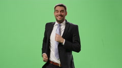 Happy businessman in a suit is running on a mock-up green screen Stock Footage