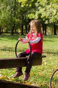 Little girl have fun in the park. Autumn season. Stock Photos