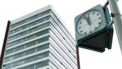 View of the public clock on the street before the modern building in the city Stock Footage