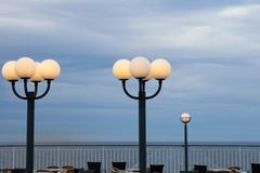 burning lamps against the storm sky - stock photo