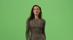 Brunette female in a dress is walking on a mock-up green screen Stock Footage