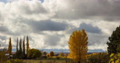 Time-lapse of Clouds Over Mountains Behind Yellow Tree in Fall Stock Footage