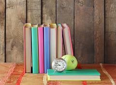 Still life with books, apple and an alarm clock. Stock Photos