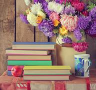Still life with books and a bouquet of asters. - stock photo