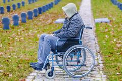 Disabled veteran in wheelchair at cemetery - stock photo