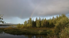 A rainbow is slowly intensifying over a forest lake in Lapland. Stock Footage