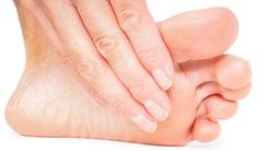 Person having pedicure, pulling hand under foot on white Stock Photos