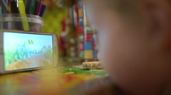Little girl watching a cartoon on the phone Stock Footage