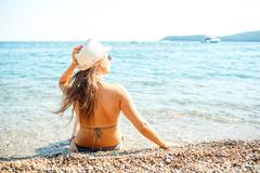 Young woman in a hat and bikini sitting on the beach - view from the back - stock photo