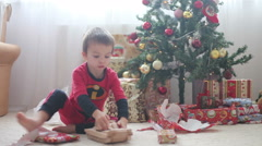Stock Video Footage of Cute boy, preschool child, opening presents on Christmas day