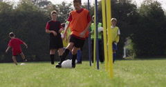Boys dribbling a soccer ball around flag poles on a sports field. Shot on RED Ep - stock footage