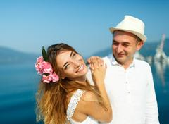 Attractive young couple walking alongside the marina on a luxury waterfront - stock photo
