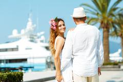 Attractive young couple walking alongside the marina with moored boats on a l Stock Photos