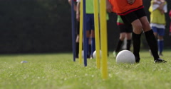 Boys dribbling a soccer ball around flag poles on a sports field. Stock Footage