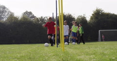 Boys dribbling a soccer ball around flag poles on a sports field. - stock footage
