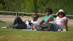 Two couples lying on grass at Trocadero Gardens in Paris Stock Footage