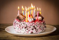 Birthday cake with burning candles Stock Photos