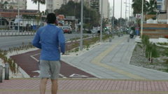Stock Video Footage of Men running on jogging track along city street. Active lifestyle for fit body