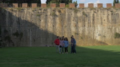 Group of young tourists walking near the stone wall of Piazza dei Miracoli, Pisa Stock Footage