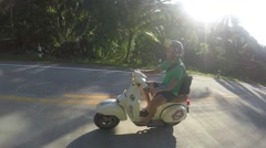 Man Riding a Vintage Scooter on Tropical Road - stock footage