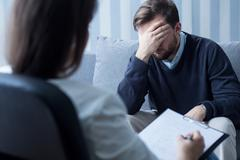 Despair man at psychologist's office - stock photo