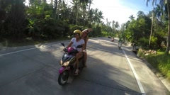 Two Summer Teenage Girls Riding Scooter on Tropical Island Stock Footage