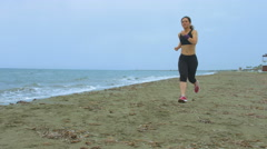 Stock Video Footage of Female athlete training at seaside, running on sandy beach. Success motivation