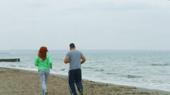 Middle-aged couple jogging on seaside beach in the morning. Healthy lifestyle Stock Footage