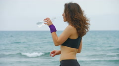 Happy young woman stops to drink water after morning run, looking into camera Stock Footage
