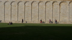 Tourists walking along the marble wall of Camposanto Monumentale, Pisa - stock footage