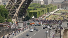 People driving, walking and gathered under the Eiffel Tower, Paris - stock footage