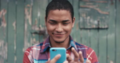 Slow Motion Portrait of mixed race man smiling using smart phone Stock Footage