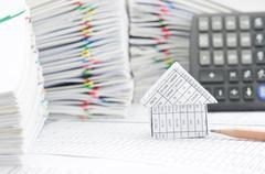 House and brown pencil have blur calculator as background Stock Photos