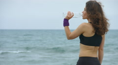 Young sportswoman feels thirsty after workout, drinking fresh water from bottle - stock footage
