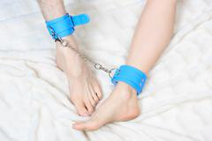male and female legs in handcuffs. couple. sex Toy - stock photo
