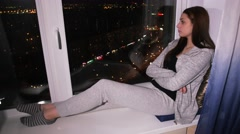 Sad woman sits on window sill, look at night city Stock Footage