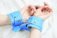 Female hands in leather handcuffs. eagerly grabbed the sheets.. sex toys Stock Photos