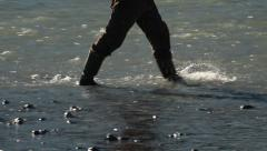 Man in Rubber Boots Walking through River Shallows Stock Footage