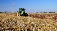Agriculture tractor plowing autumn time farm field with corn stalks Stock Footage