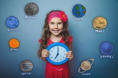 Teen girl laughs holding her hands round the clock blue planet o - stock photo