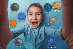 Teen girl making a self laughing mouth open planet of the solar - stock photo
