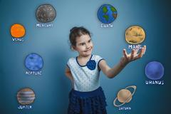 teen girl smiling and holding a news space planet Mars planet of - stock photo