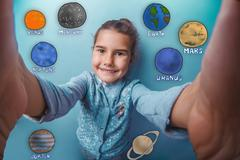 Stock Photo of Teen girl smiling and removes self planets of the solar system a