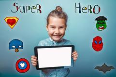 girl holding the tablet and rejoice smile super hero super power - stock photo