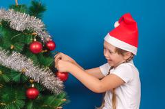 The girl in a red cap hangs up on a fir-tree with tinsel a toy and smiles Stock Photos